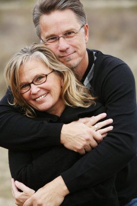 Middle aged couple holding each other wearing glasses